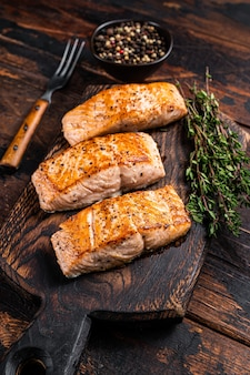 Steaks de filet de saumon frit sur une planche de bois au thym. fond en bois sombre. vue de dessus.
