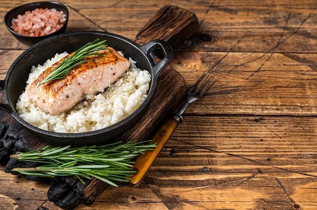 Steaks de filet de saumon grillé avec du riz blanc dans une casserole. fond en bois. vue de dessus. espace de copie.