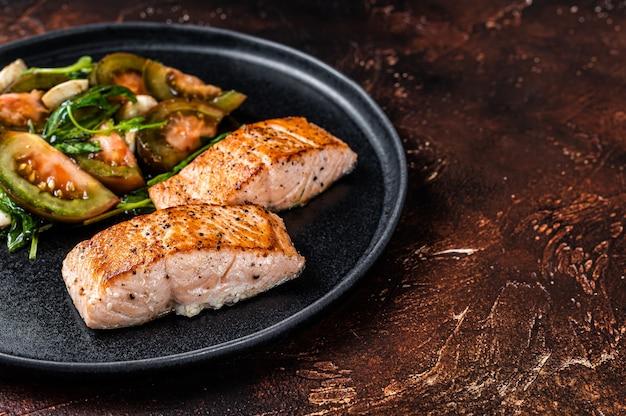 Steaks de filet de saumon grillé avec roquette et salade de tomates sur une assiette