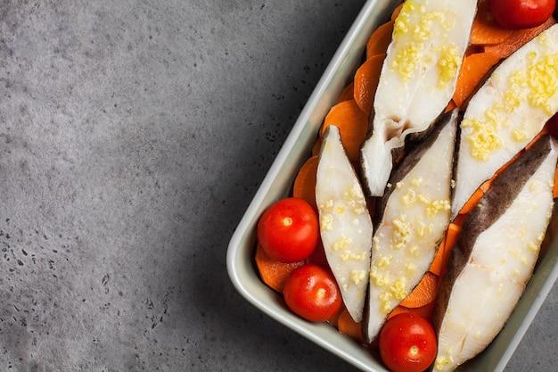 Steaks de flétan réfrigérés dans un plat allant au four avec tomates et patates douces