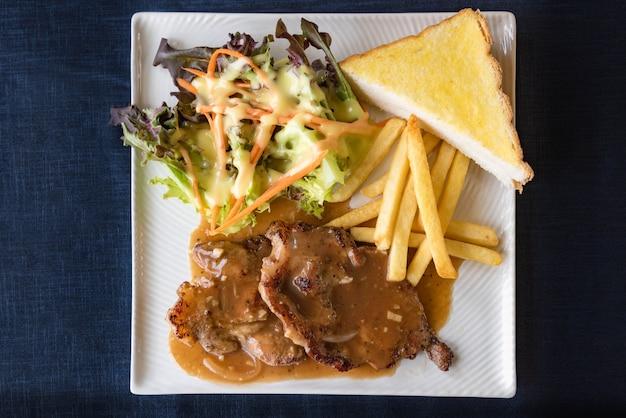 Steaks grillés, frites bouillies et salade de légumes