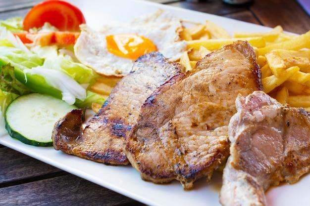 Steaks grillés, frites, oeuf au plat et légumes