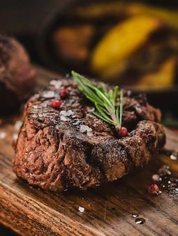 Steaks grillés sur une planche à découper en bois. de succulentes portions juteuses épaisses de steak de filet grillé servi avec des pommes de terre rôties sur une vieille planche de bois.