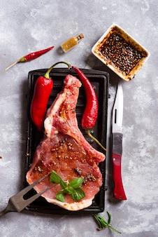 Steaks et poêles crues avec assaisonnements, garnitures et ingrédients