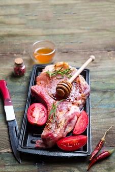Steaks et poêles crus avec assaisonnement, garnitures et ingrédients sur un dos rustique foncé