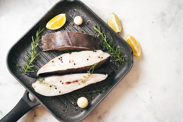 Steaks de poisson de flétan crus préparés pour griller dans une poêle