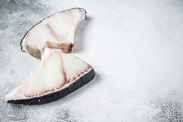 Steaks de poisson requin cru sur une table de cuisine.
