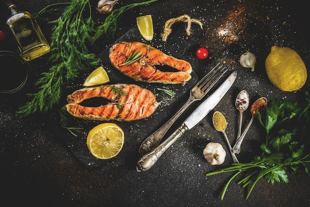 Steaks de poisson de saumon grillé avec des ingrédients citron, herbes, huile d'olive, planche à découper en ardoise, table rouillée foncée