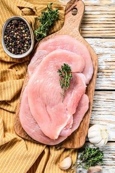 Steaks de poitrine de dinde sur une planche à découper. viande de volaille fraîche. vue de dessus