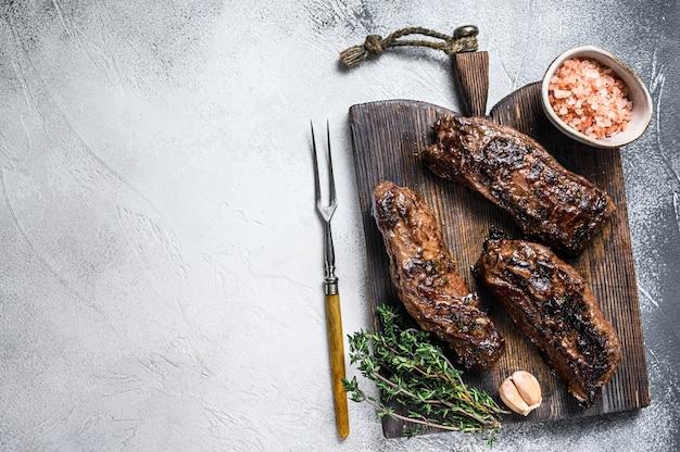 Steaks de poitrine grillés à la sauce barbecue sur une planche de bois sur blanc. vue de dessus.