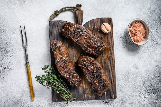 Steaks de poitrine grillés à la sauce barbecue sur une planche de bois