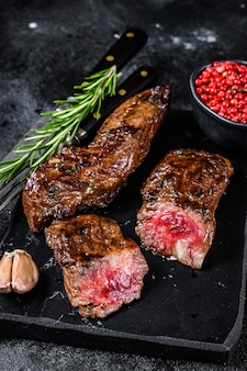 Steaks de poitrine grillés à la sauce barbecue sur une planche de marbre sur table en bois. vue de dessus.