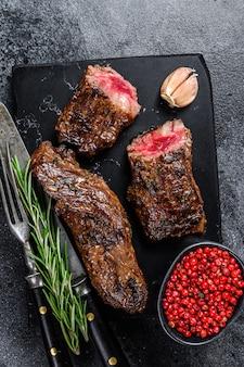 Steaks de poitrine grillés à la sauce barbecue sur une planche de marbre
