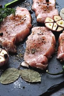 Steaks de porc cru à l'ail et aux épices sur une planche en pierre. le concept de cuisson de la viande. régime céto. régime paléo. régime pegan.