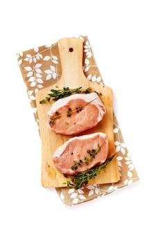 Steaks de porc cru frais sur une planche à découper