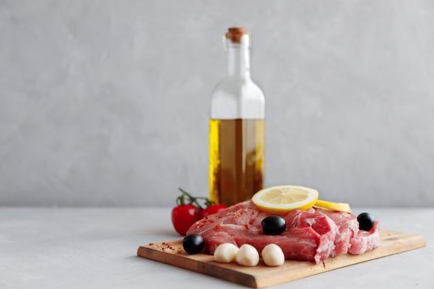 Steaks de porc cru sur une planche de bois marinée aux épices.