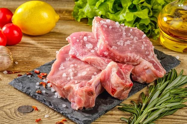 Steaks de porc cru sur un plateau en pierre avec herbes, tomates, ail et citron.