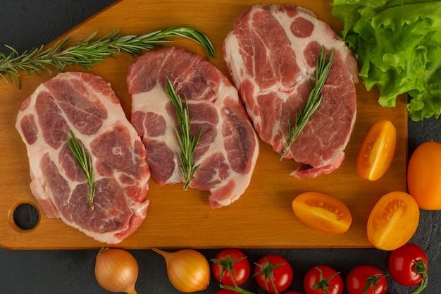 Steaks de porc cru - prêts à cuire avec des herbes et des tomates. fond en bois.