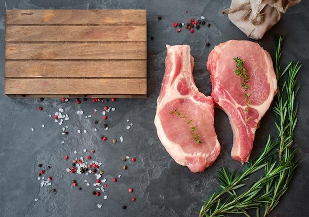 Steaks de porc cru sur la vue de dessus de fond de pierre noire