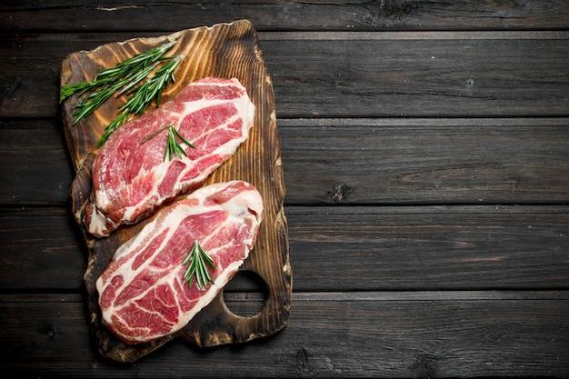 Steaks de porc crus au romarin. sur un fond en bois.