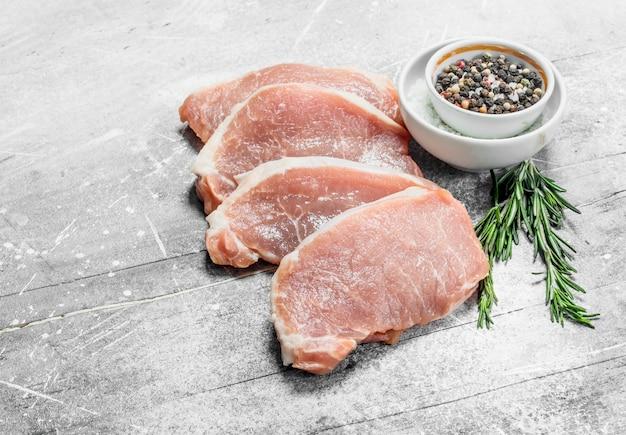 Steaks de porc crus aux épices et herbes. sur une surface rustique.