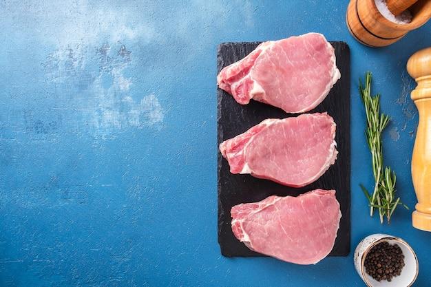 Steaks de porc crus aux épices vue de dessus espace pour le texte