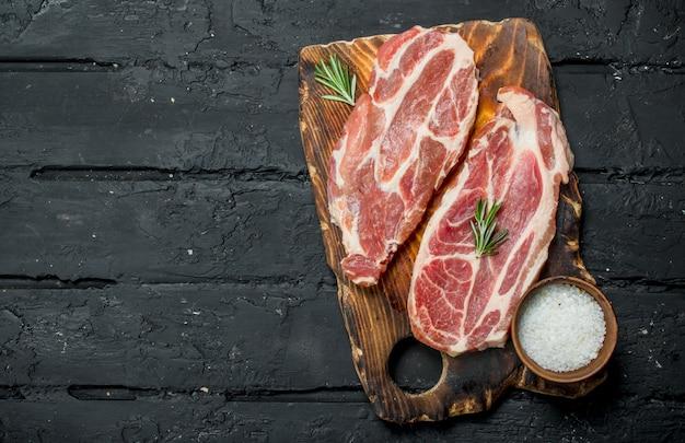Steaks de porc crus aux herbes aromatiques et aux épices. sur un fond rustique noir.