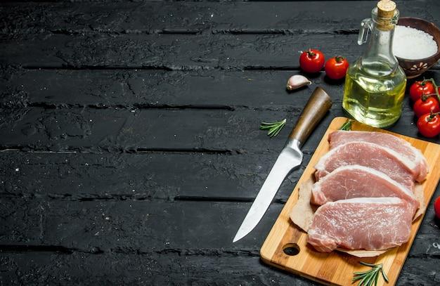 Steaks de porc crus aux tomates et épices. sur un fond rustique noir.