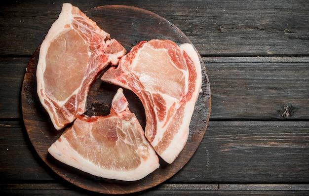 Steaks de porc crus sur l'os. sur un fond en bois.