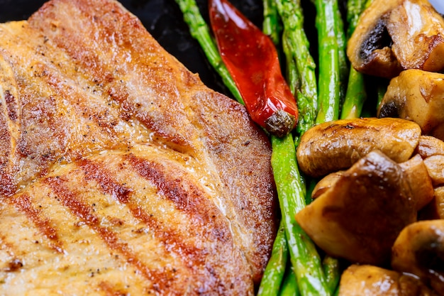 Steaks de porc grillé aux herbes, asperges, champignons ardoise pierre fond sur bois se bouchent.