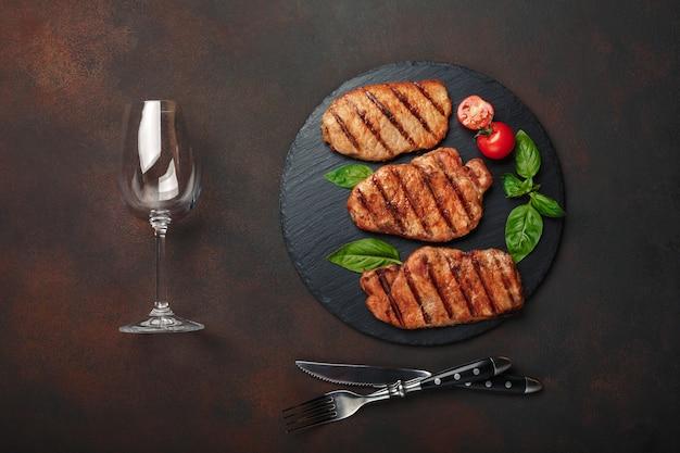Steaks de porc grillés au basilic, tomates, couteau, fourchette et verre à vin sur pierre noire et fond rouillé brun