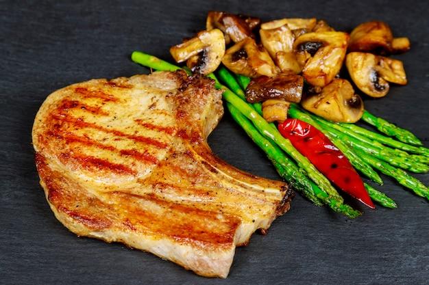 Steaks de porc grillés aux herbes, asperges, champignons sur fond ardoise