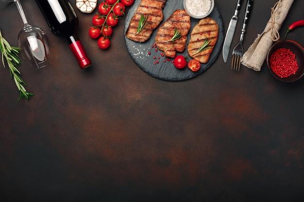 Steaks de porc grillés sur pierre avec bouteille de vin, verre à vin, couteau et fourchette sur fond rouillé