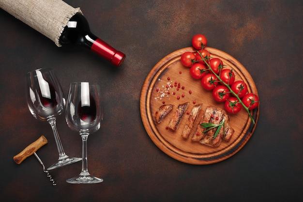 Steaks de porc grillés en tranches avec bouteille de vin, verre à vin, tire-bouchon, tomates cerises et romarin
