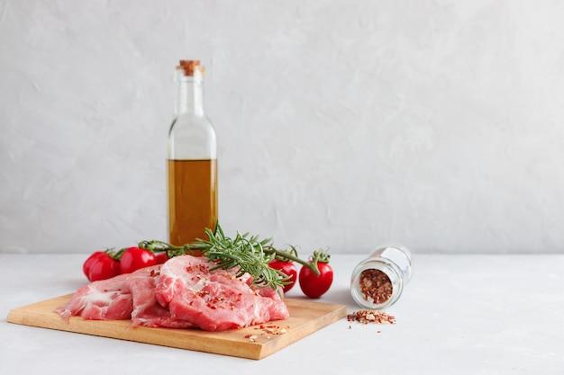 Steaks de porc sur une planche de bois, en arrière-plan une bouteille d'huile d'olive, tomates cerises et épices