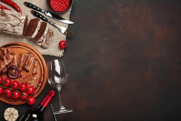 Steaks de porc tranchés avec bouteille de vin, verre à vin, tire-bouchon, couteau, fourchette, pain noir, tomates cerises