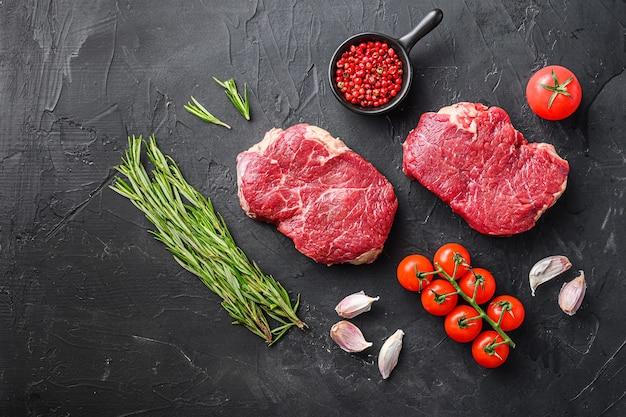Steaks de rumsteck crus à partir de coupes de viande de bœuf biologique avec romarin, ail et épices sur fond texturé noir, espace de vue de dessus pour le texte.