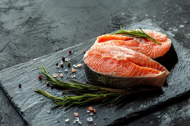 Steaks de saumon cru et ingrédients sur la planche. poisson rouge frais au romarin, sel et poivre. steak de poisson aux épices sur une surface noire. morceaux de poisson frais. un lieu pour le copywriting