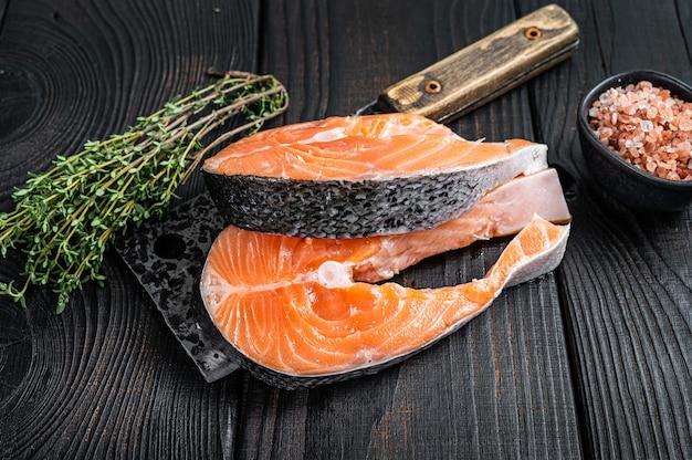 Steaks de saumon crus frais sur couperet de boucher. fond en bois noir. vue de dessus.