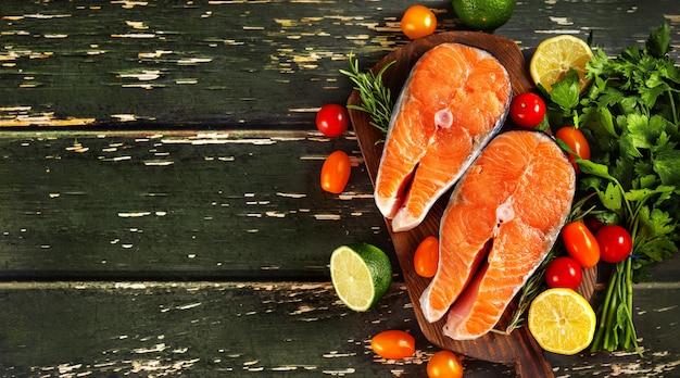 Steaks de saumon frais au citron, tomates cerises et persil sur mur en bois vert.