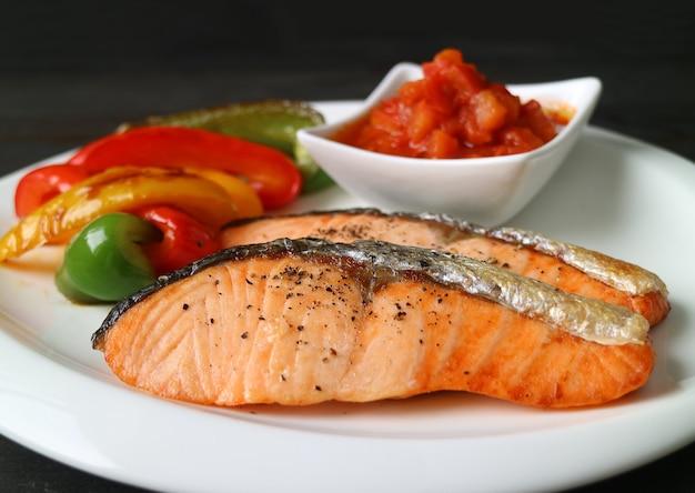 Steaks de saumon poêlés maison avec légumes colorés grillés et salsa