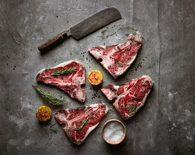 Steaks t-bone crus sur du béton gris texturé.