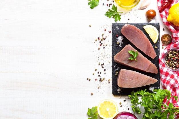 Steaks de thon cru frais sur plaque d'ardoise noire sur fond blanc