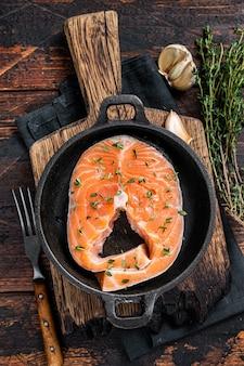 Steaks de truite ou de saumon crus dans une poêle au thym. fond en bois sombre. vue de dessus.