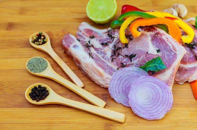 Steaks de viande crue avec planche à épices.