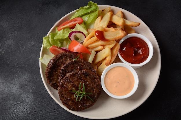 Steaks de viande de hamburger frites et salade sur fond noir