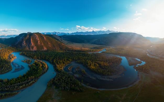 Steppe kurai et rivière chuya sur fond de montagnes de la crête du nord-chui. montagnes de l'altaï, russie. image panoramique de drone aérien.