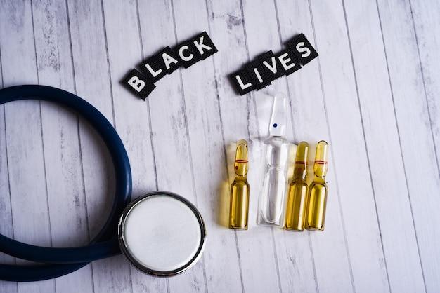 Stéthoscope et ampoules médicales et inscription vies noires