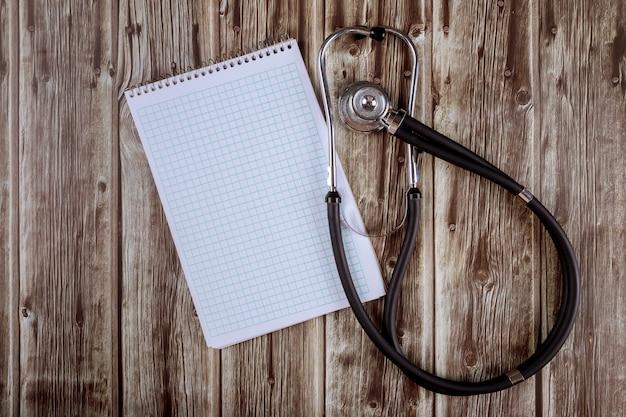 Stéthoscope et cahier en papier sur une tablette en bois