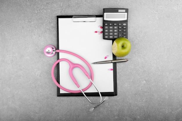 Stéthoscope, calculatrice, pomme et presse-papiers sur table
